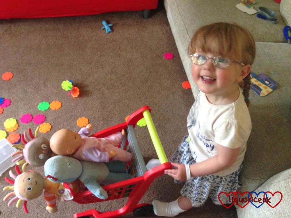 Jessica pushing some of her dollies around in a toy trolley