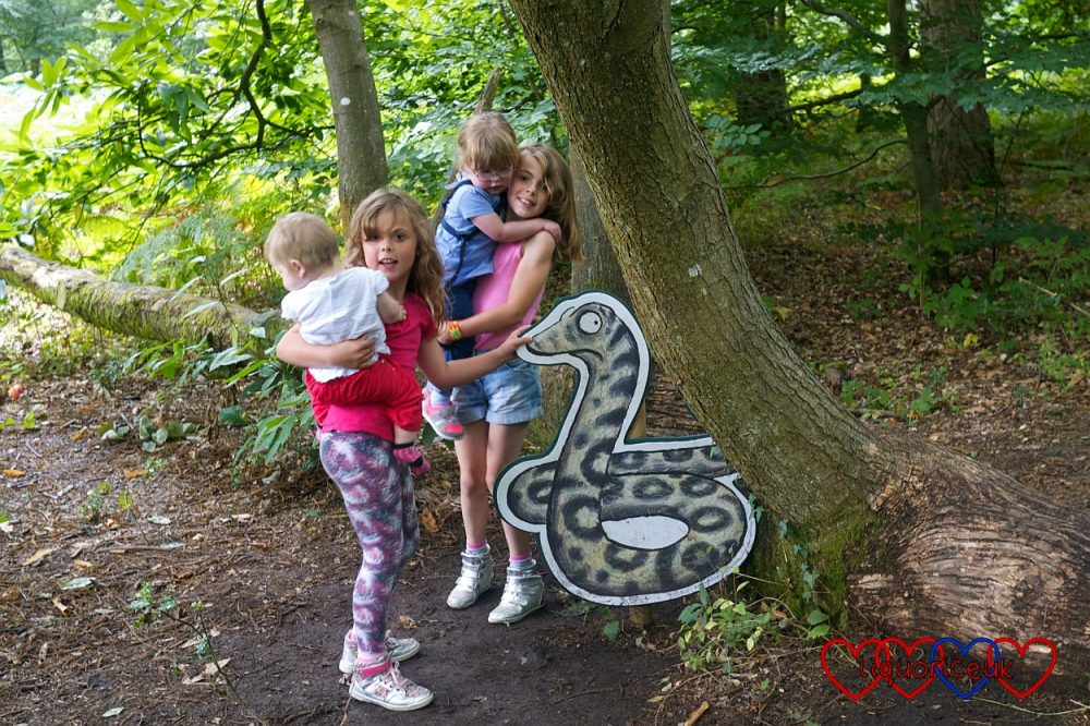 Jessica and Sophie with their cousins standing next to the Snake on the Gruffalo trail at Alice Holt Forest