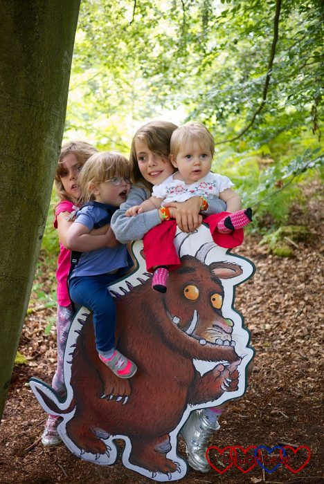 Jessica and Sophie with their cousins standing by a cut-out Gruffalo on the Gruffalo trail at Alice Holt Forest