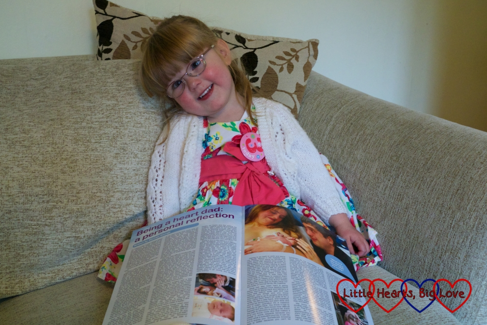 Jessica on her 3rd birthday holding a Little Hearts Matter newsletter open to an article written by her daddy