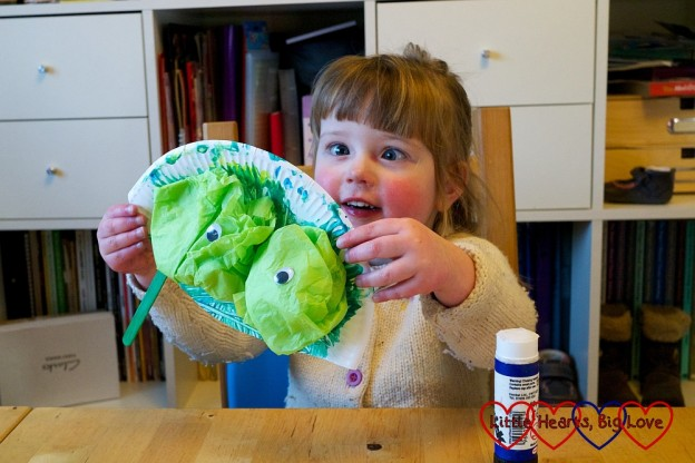 Jessica holding up a frog mask made from a paper plate