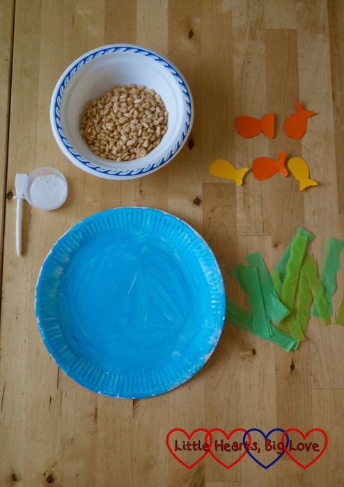 A blue paper plate, glue, puffed rice cereal, cardboard fish shapes and tissue paper strips