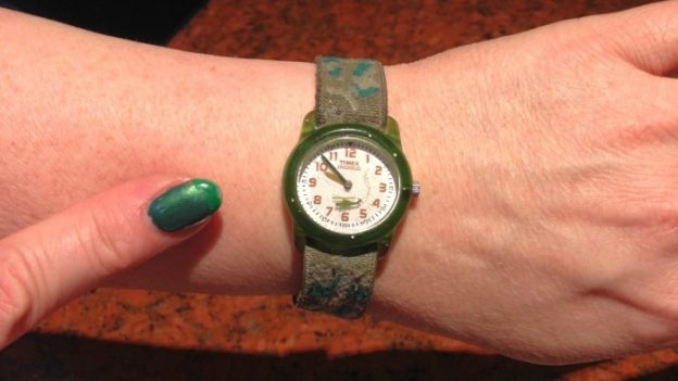 A finger pointing to the time on a wristwatch