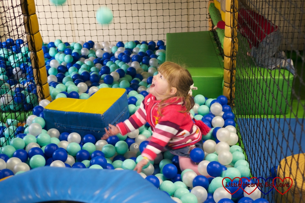 Jessica throwing balls in the air in a ball pit