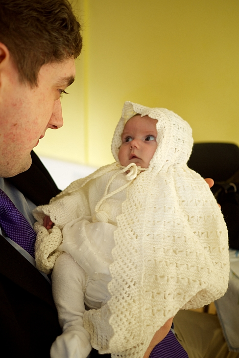 Jessica in her christening shawl looking at Daddy