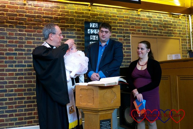 Sophie being baptised by our minister while hubby and I look on