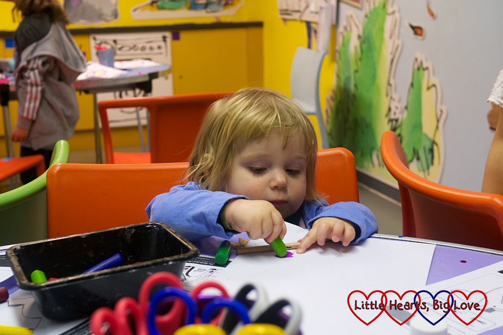Sophie scribbling with a crayon in George's Crafty Kitchen