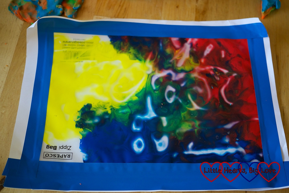 Paint inside a ziplock page with white marks where a picture has been 'drawn' on