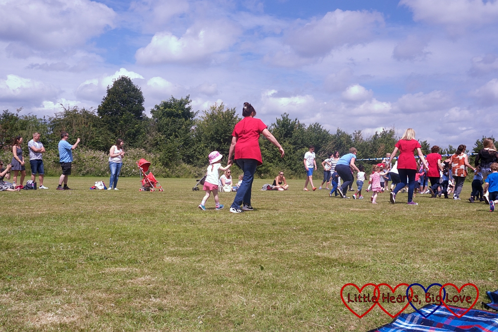 Jessica running towards the finish line with the other children