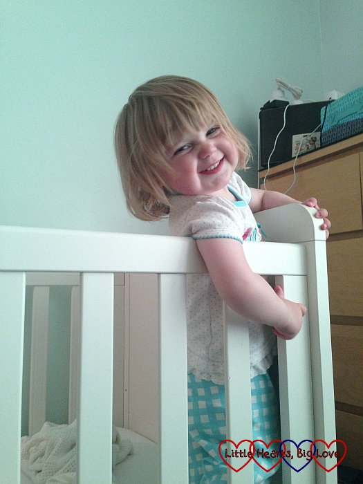 Sophie standing in her cot, giving us a cheeky grin while resisting bedtime