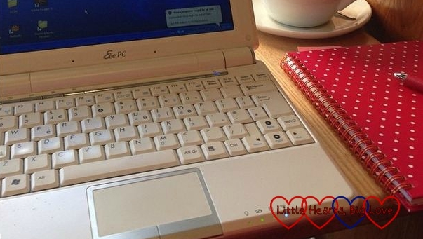 A laptop keyboard with a notepad next to it
