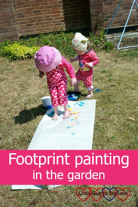 Jessica and Sophie doing footprint painting in the garden