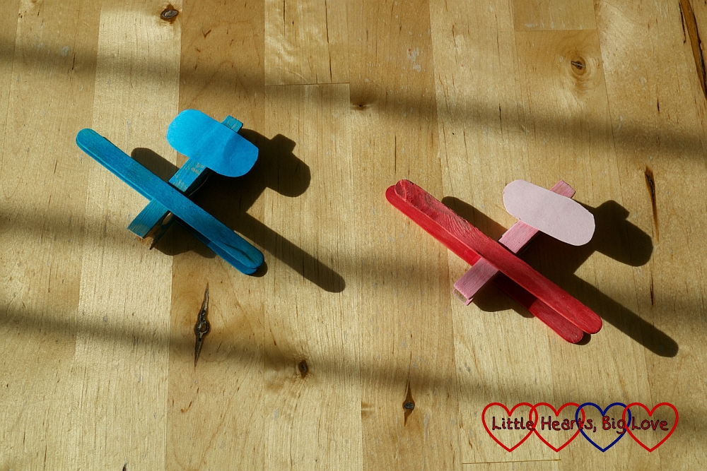 Two aeroplanes - one blue, one red - made from a peg and craft sticks