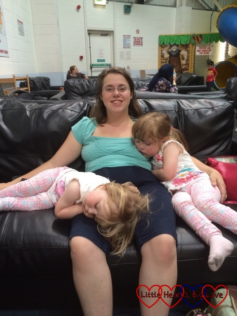 Me sitting ona sofa at soft play with two children asleep on my lap