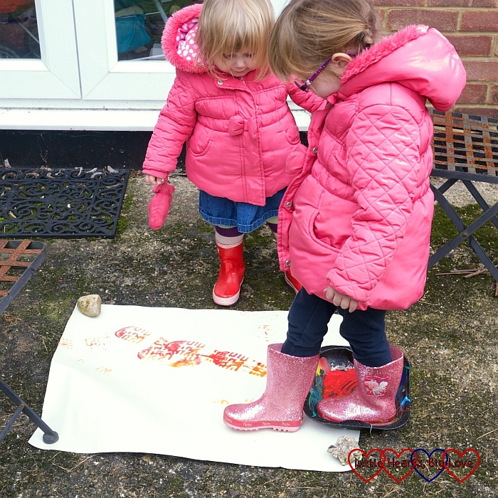 Jessica and Sophie doing some footprint painting wearing welly boots