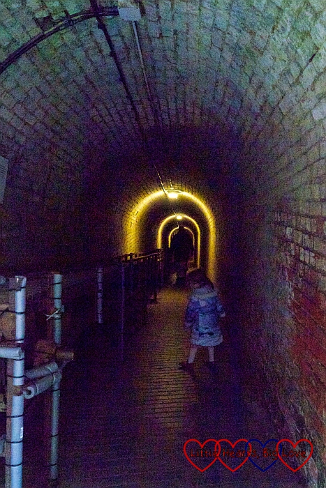 Sophie walking through a tunnel at Fort Nelson