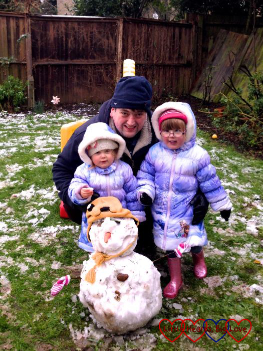 Hubby, Jessica and Sophie with their snowman in the garden