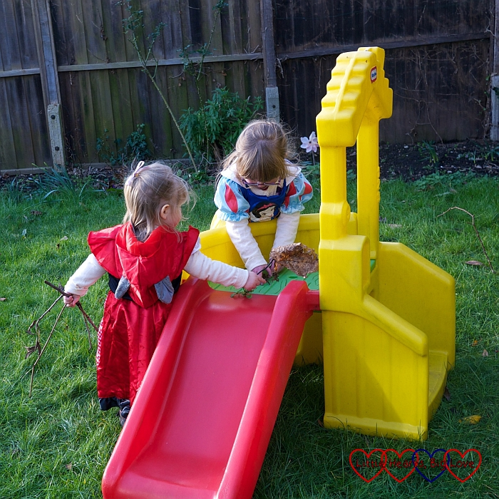 Little Red Riding Hood and Snow White playing on the slide.