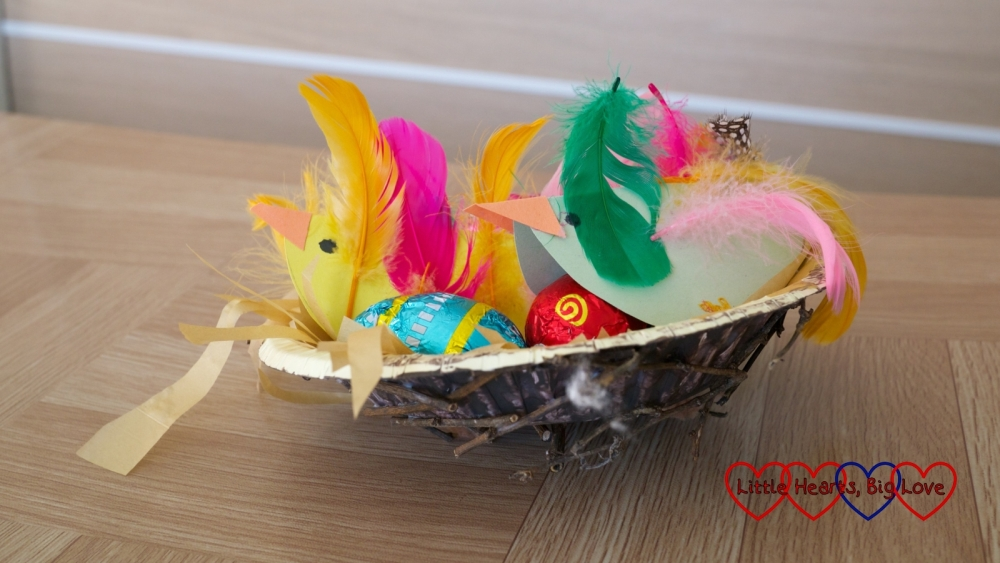 A paper bowl nest with twigs glued to it and paper birds inside covered in feathers looking after small chocolate eggs