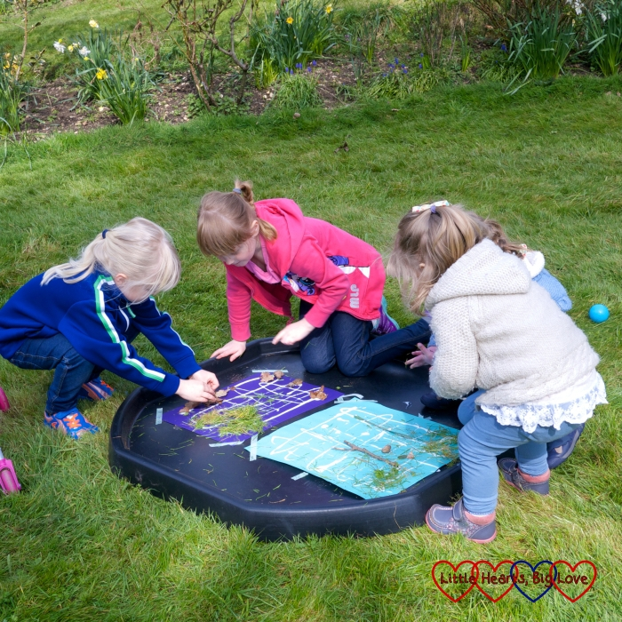 Four cousins working together to create a nature collage in the garden in Spring