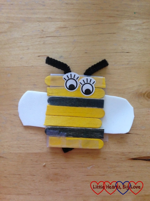 A bee made from craft sticks and white craft foam