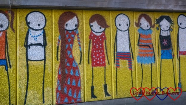 A street art mural showing lots of different people