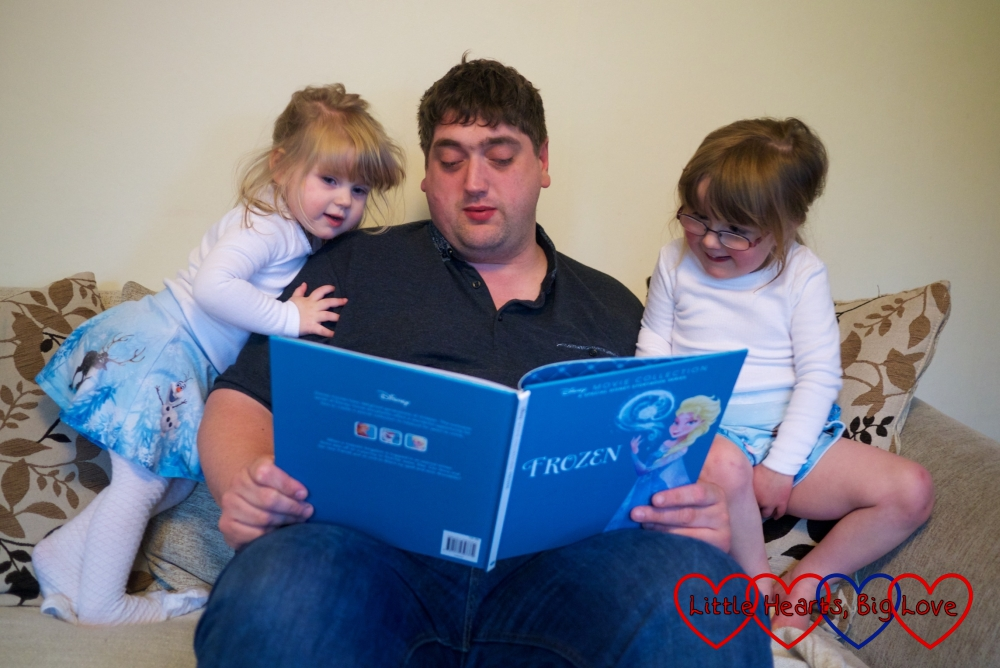 Daddy reading Frozen to the girls