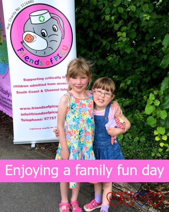 Willow and Jessica - two little heart warriors standing in front of a Friends of PICU banner at the Friends of PICU family fun day