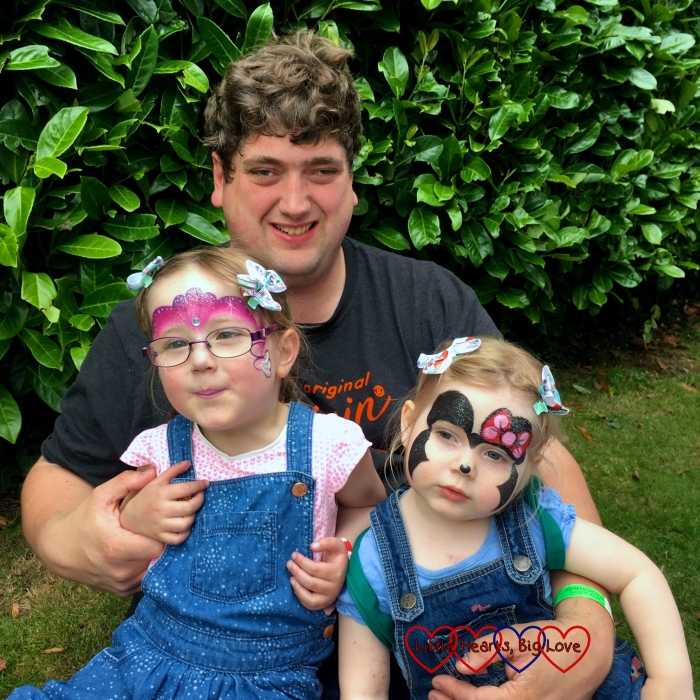 Jessica and Sophie with their faces painted sitting on Daddy's lap