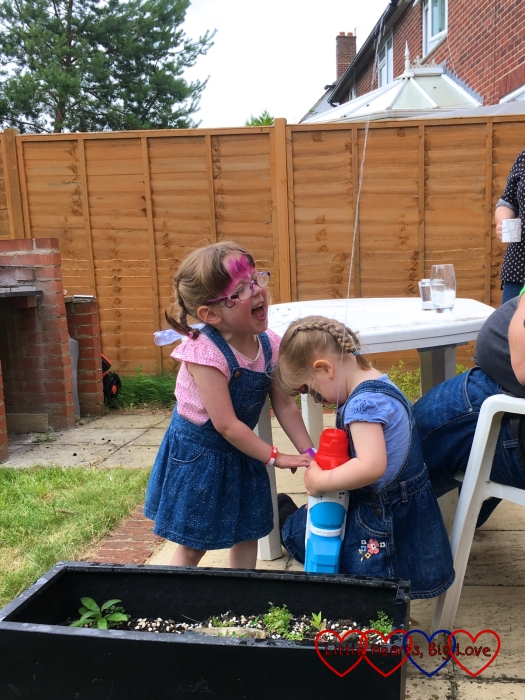 Jessica and Sophie having a water fight in our friends' garden