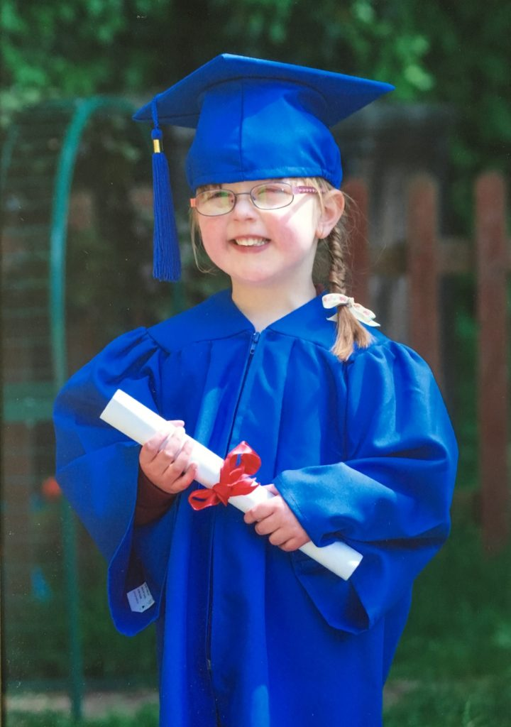 Jessica in her blue graduation gown in her preschool graduation photo