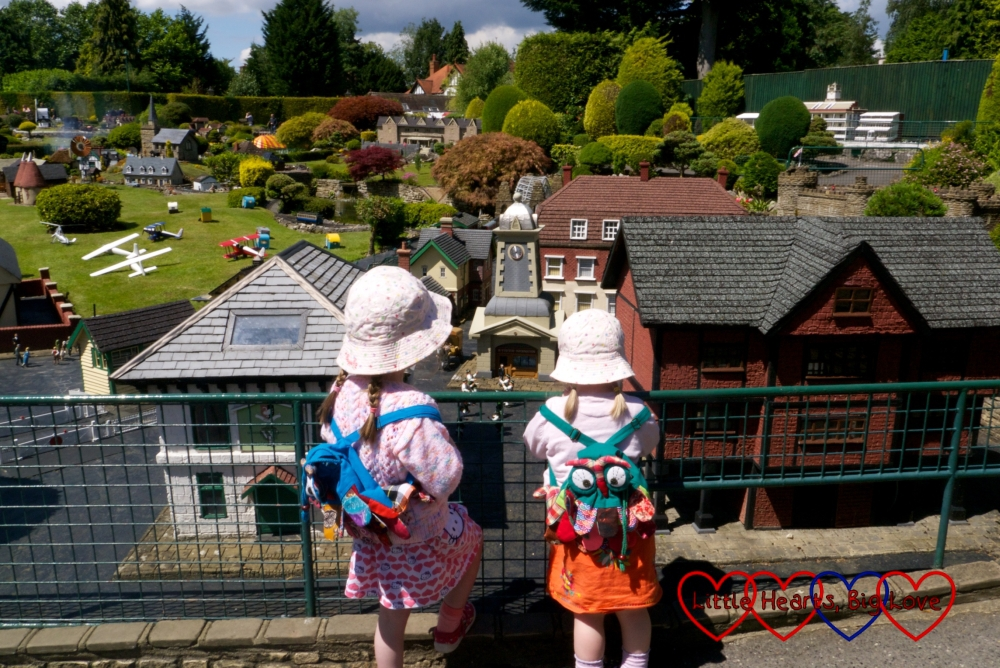 Jessica and Sophie with owl backpacks on standing in front of the model village at Bekonscot