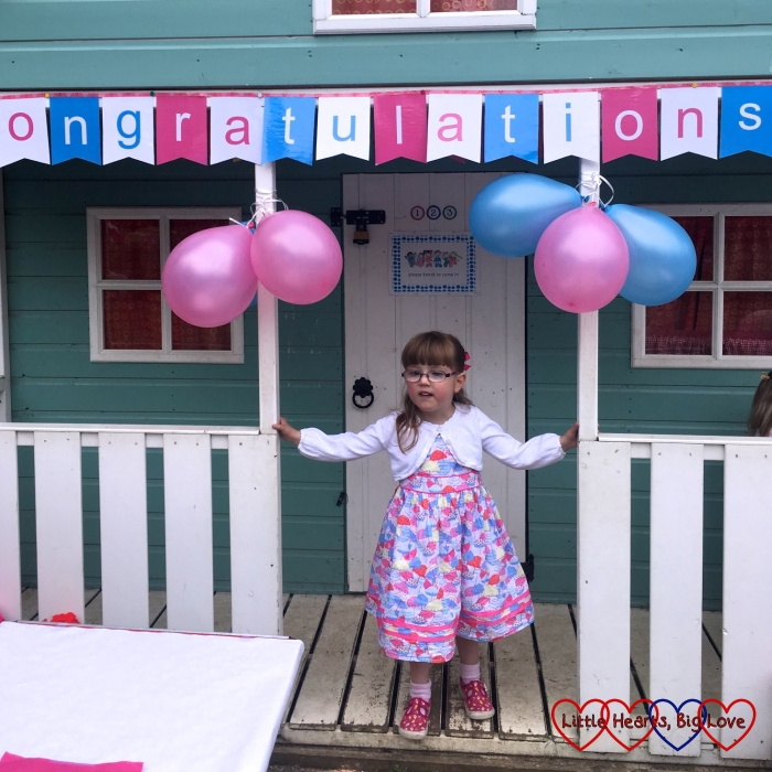 "Jessica standing in front of the playhouse at preschool with a banner saying ""Congratulations"" over her head at her preschool leavers' party"