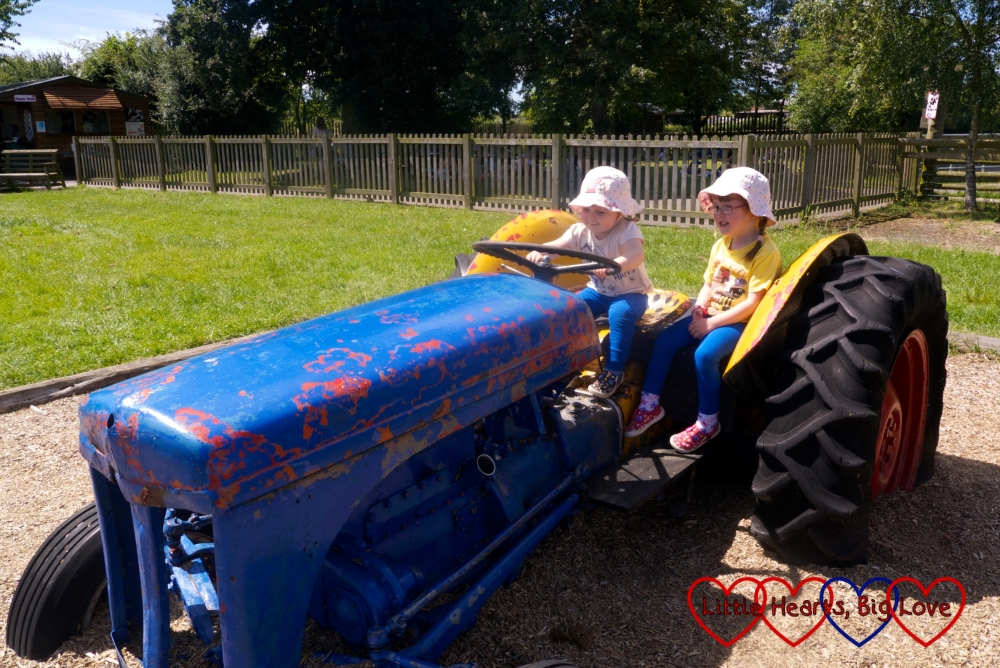 Jessica and Sophie driving a blue tractor in the play area at Odds Farm Park