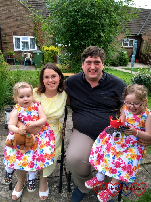 Me, hubby, Jessica and Sophie sitting on the bench in my mum's back garden all dressed up and ready to go to my sister's birthday party