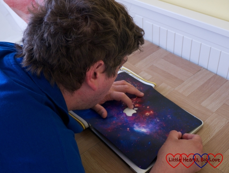 Hubby applying the Crazy Galaxy skin to his MacBook Pro