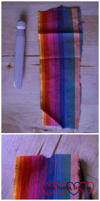 A piece of fabric next to the clothes peg to show suggested size and showing the hole cut out in from the fold