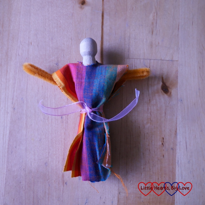 A clothes peg with pipe cleaner arms and fabric gathered around the middle, secured with a ribbon
