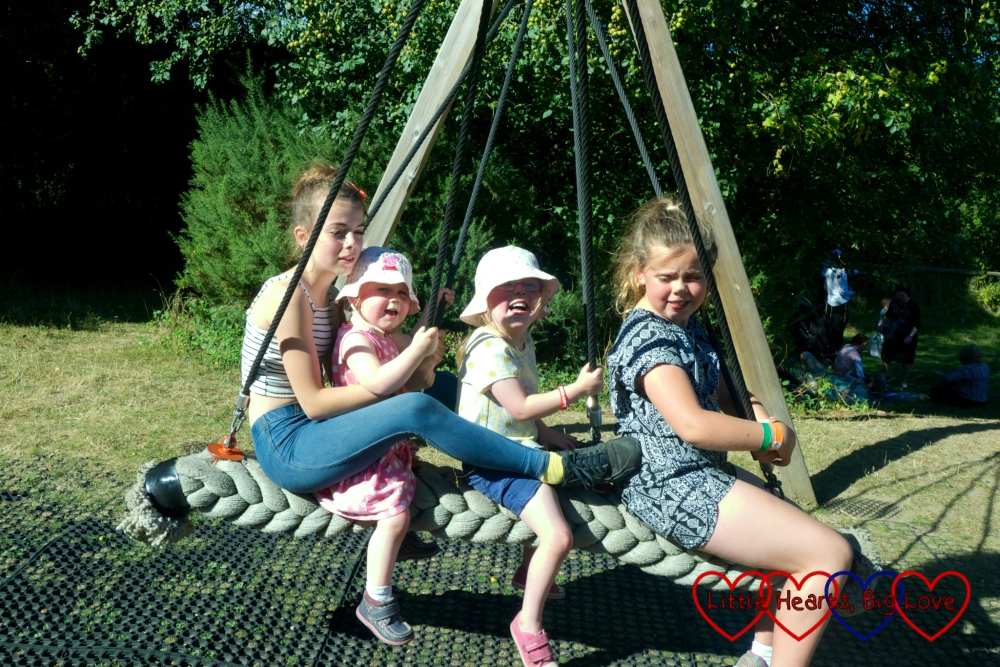 Jessica and Sophie swinging on a big rope swing with their cousins