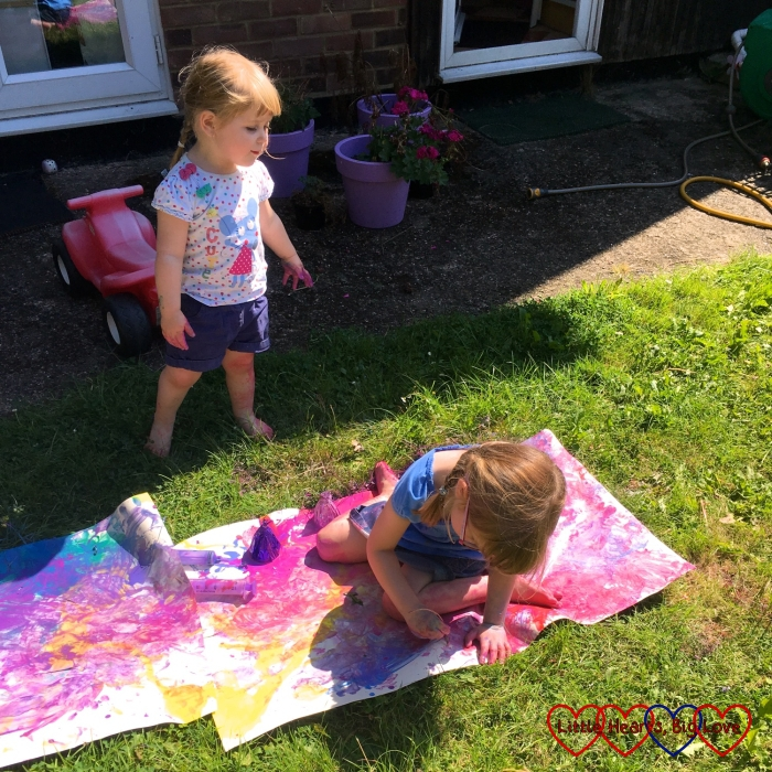 Jessica sitting and smearing paint over lining paper in the garden while Sophie watches