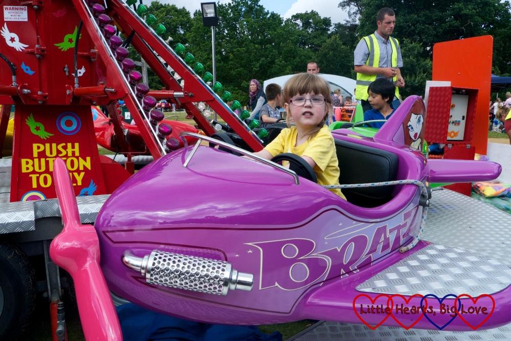 Jessica flying a purple aeroplane on the aeroplane ride