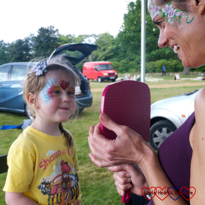 Jessica looking in the mirror having just had her face painted with pretty patterns across her forehead and around her eyes and a red heart in the middle