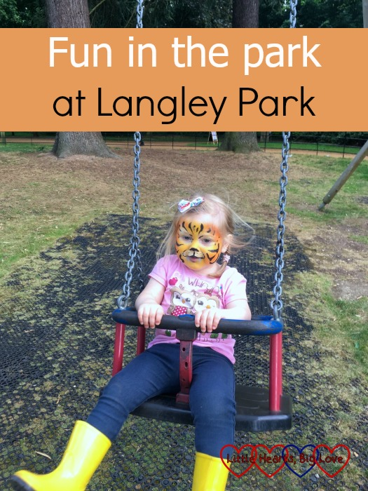 Sophie with her face painted like a tiger on a swing at Langley Park