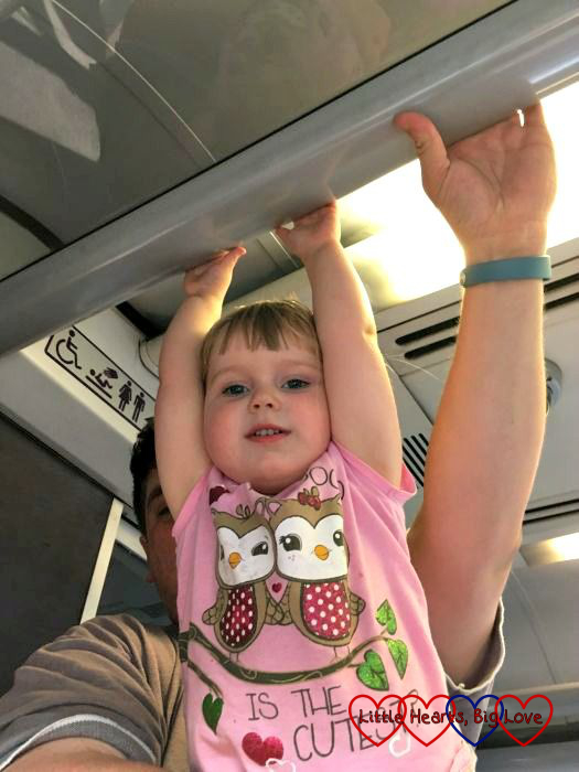 Sophie swinging from the luggage rack (while being held by Daddy)