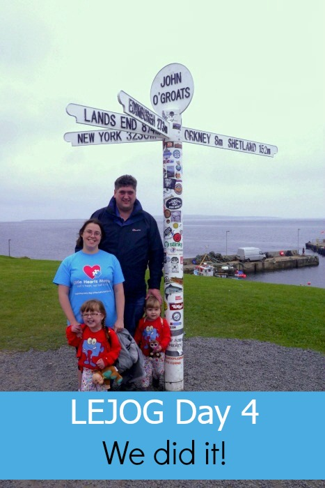 "Me, hubby, Jessica and Sophie standing in front of the signpost at John O'Groats with the text ""LEJOG Day 4 - We did it!"""