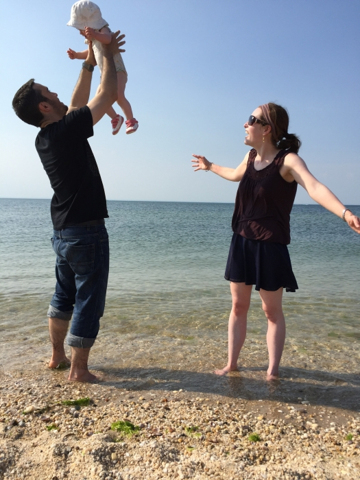 Katie from Squirmy Popple with her husband Adrian and baby Popple, standing on a beach with Adrian holding Popple in the air