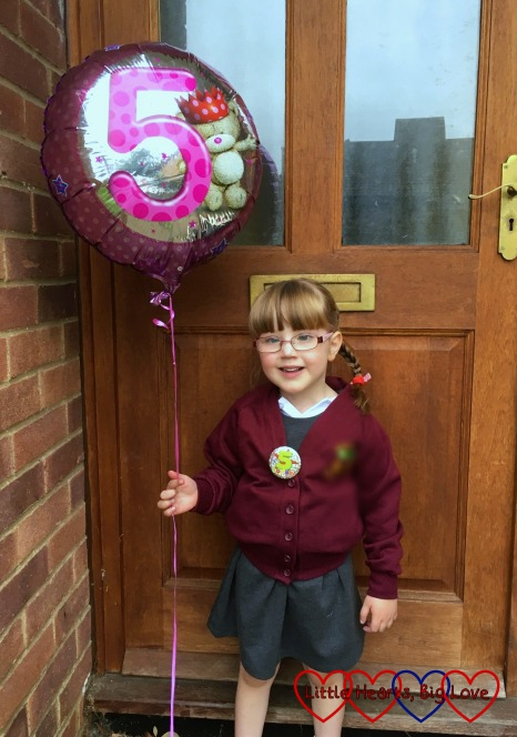 Jessica standing outside the front door on her 2nd day of school holding her birthday balloon with a number 5 on it