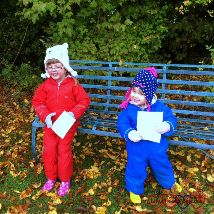 Jessica in her red puddlesuit and Sophie in a blue puddlesuit sitting on a bench at Chiltern Open Air Museum with their scavenger hunt leaflets