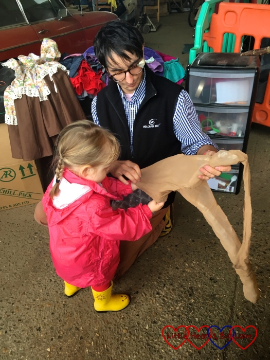 Sophie stuffing bubble wrap into tights to make the arms of our scarecrow