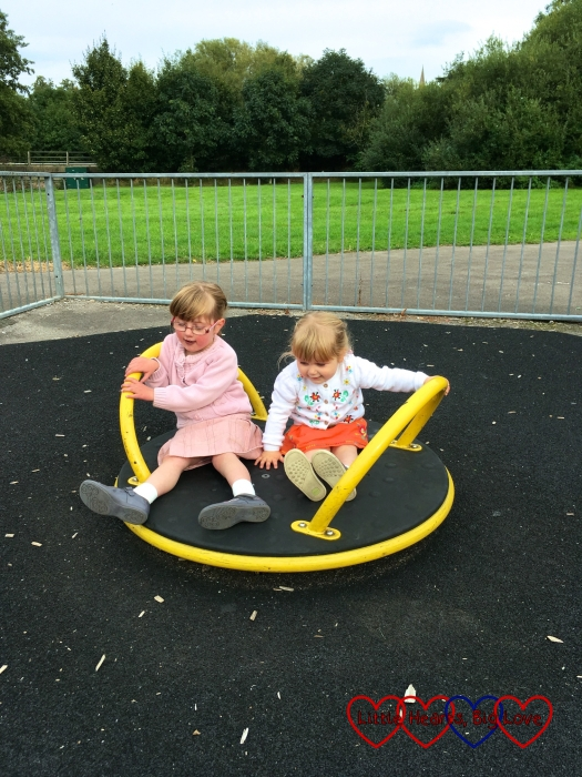 Sophie and Jessica spinning on the roundabout